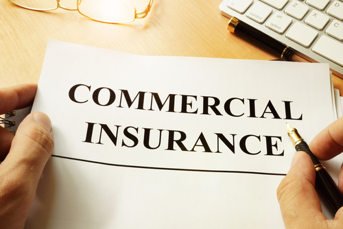 person holding paper that says commercial insurance