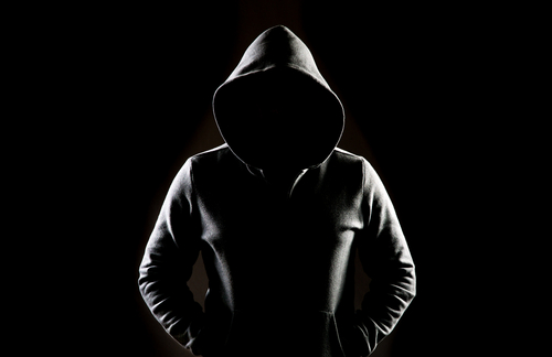 person standing in the dark with a hoodie on
