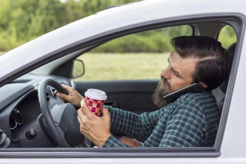 man driving while on the phone holding coffee