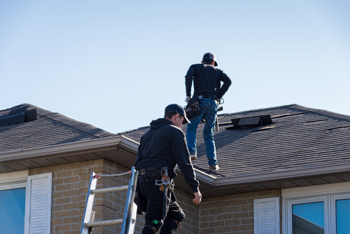 two workers inspecting damage on roof