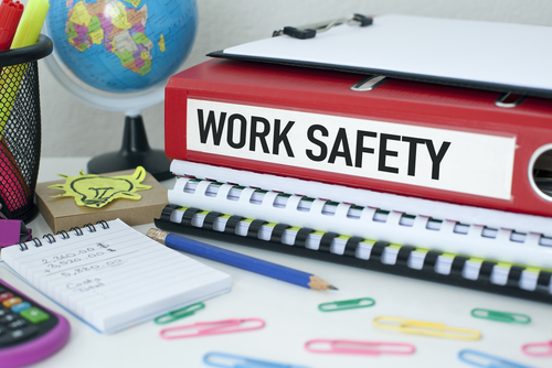 binder with work safety written on it, surrounded by notes, paperclips, other notebooks