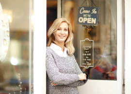 woman standing outside open business