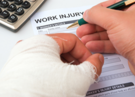close-up on injured hand filling out workers compensation paperwork